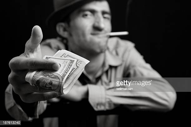 Photo of cruel man with fedora hat giving dollar bills