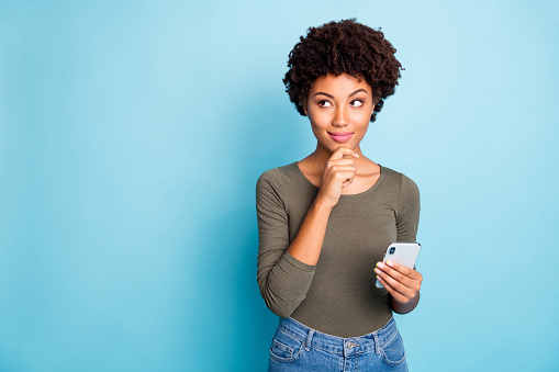 Photo of cunning smirking puzzled interested dark skinned youngster touching her chin in thought of what to post to her profile on social media wearing jeans denim isolated over vivid color blue background 1180231917