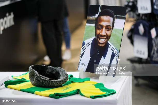 A photo of Cyrille Regis is seen behind a shirt and cap during the Cyrille Regis Memorial Service at The Hawthorns on January 30 2018 in West...