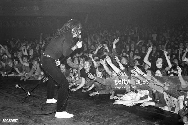 Photo of David COVERDALE and WHITESNAKE David Coverdale performing live onstage with front rows of fans in audience reaching up and cheering