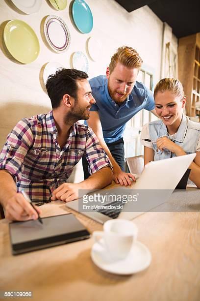 Photo of  designer team working together in graphic studio.