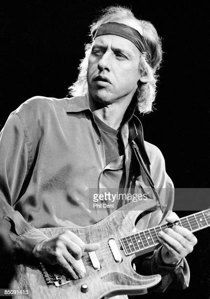 Photo of DIRE STRAITS and Mark KNOPFLER Mark Knopfler performing live onstage playing Pensa guitar wearing headband