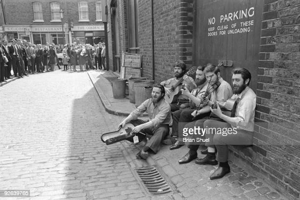 Photo of DUBLINERS Group portrait at the back of Transatlantic Records in Marylebone being watched by the public LR Ciaran Bourke Bob Lynch Barney...