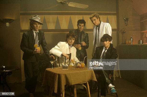 Photo of DURAN DURAN LR Nick Rhodes John Taylor Roger Taylor Simon Le Bon Andy Taylor in bar set posed studio group shot
