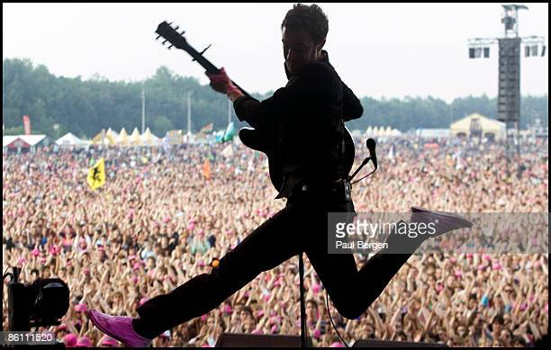 FESTIVAL Photo of EDITORS and Tom SMITH Tom Smith performing on stage jumping audience