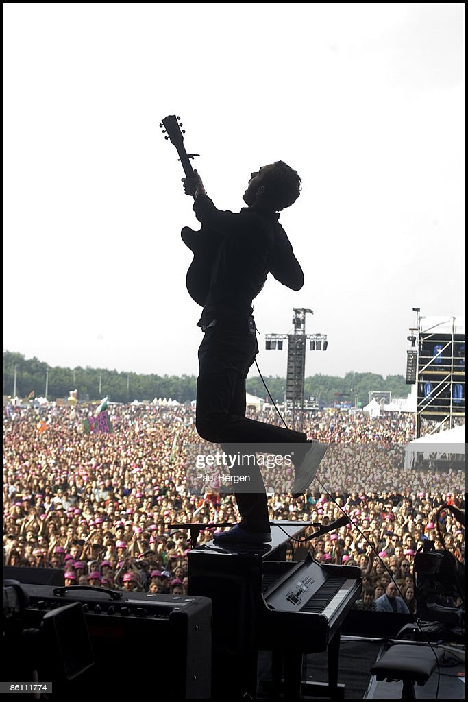 FESTIVAL Photo of EDITORS and Tom SMITH, Tom Smith performing on stage, standing on piano, audience