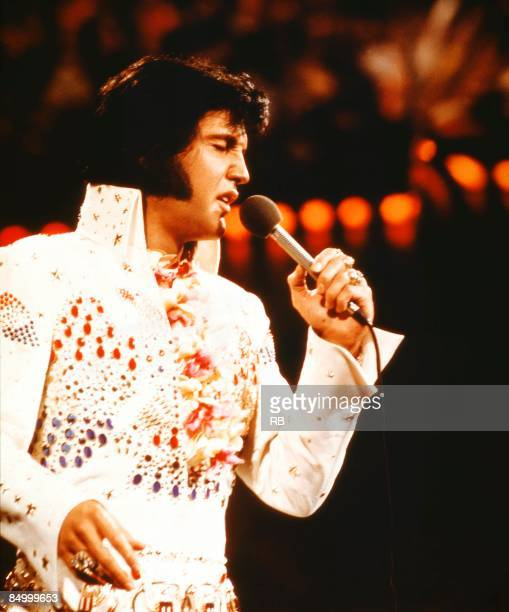 Photo of Elvis PRESLEY Elvis Presley performing live onstage at 'Aloha From Hawaii' concert wearing white jumpsuit