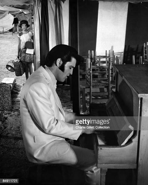 Photo of Elvis PRESLEY posed playing piano with sideburns clate 1960s