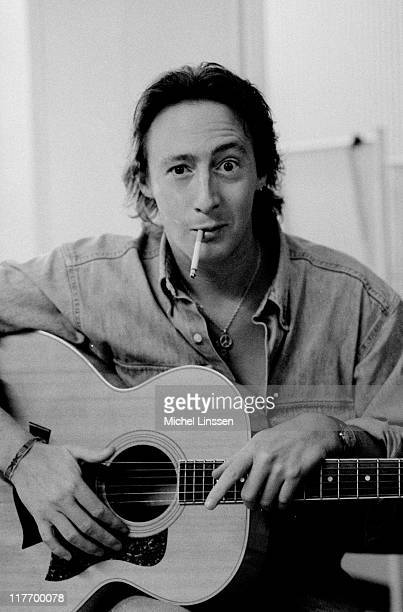 Photo of English musician and actor Julian Lennon posed with acoustic guitar and cigarette in the Netherlands in 1992