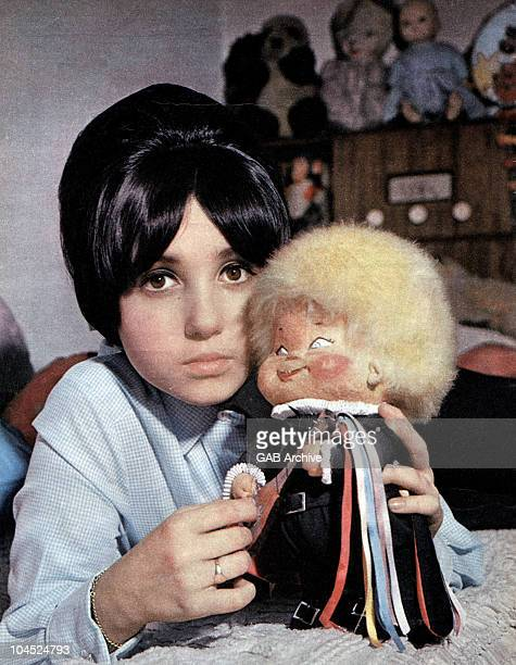 Photo of English singer and actress Adrienne Posta holding a doll