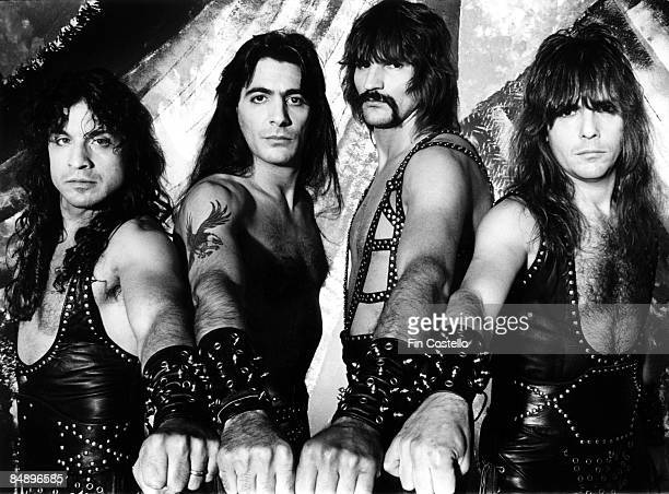 Photo of Eric ADAMS and Scott COLUMBUS and MANOWAR and Ross FRIEDMAN and Joey DeMAIO Posed studio group portrait arms out LR Eric Adams Joey DeMaio...