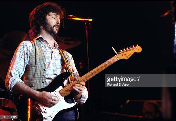 Photo of Eric CLAPTON performing live onstage playing 'Blackie' Fender Stratocaster guitar holding cigarette under guitar strings