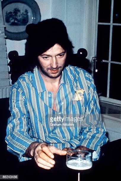 Photo of Eric CLAPTON posed at home in Ewhurst Surrey reaching for pint of beer
