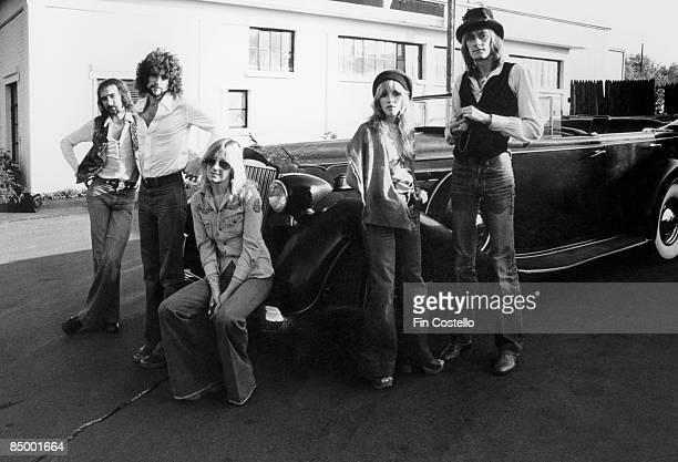 Photo of FLEETWOOD MAC, L-R: John McVie, Lindsey Buckingham, Christone McVie, Stevie Nicks, Mick Fleetwood - posed, group shot, by car - MusicBrainz:...