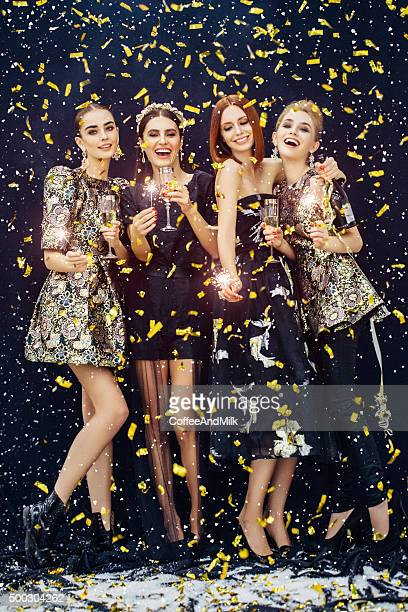 Photo of four laughing girls strewn confetti and snow