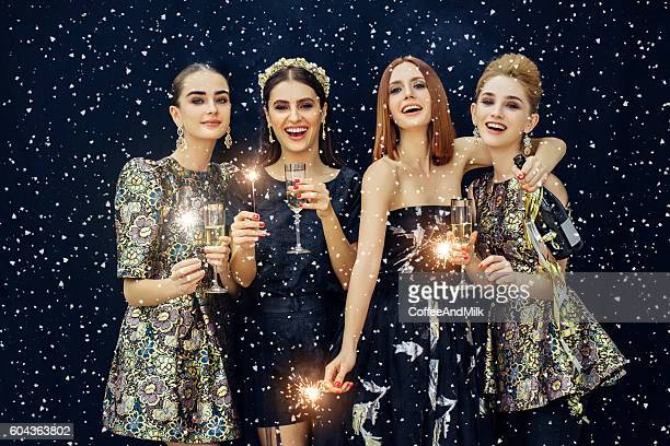 Photo of four laughing girls strewn snow