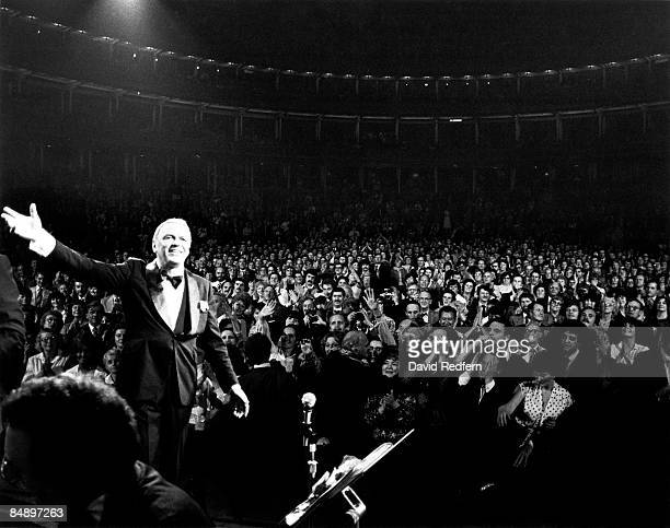 HALL Photo of Frank SINATRA performing live onstage waving with audience visible behind