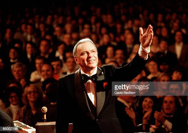Photo of Frank SINATRA, performing live onstage, waving, with audience behind.