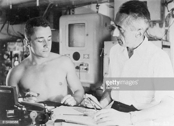 Photo of french seafarer Jacques Cousteau and a bare chested member of his crew plotting out their ship's course