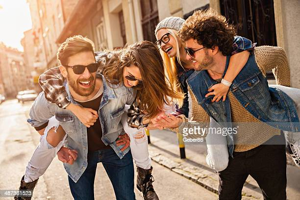 photo of friends having fun in city - piggyback stock pictures, royalty-free photos & images