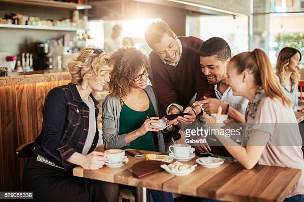 Photo of friends looking at a phone in a cafe