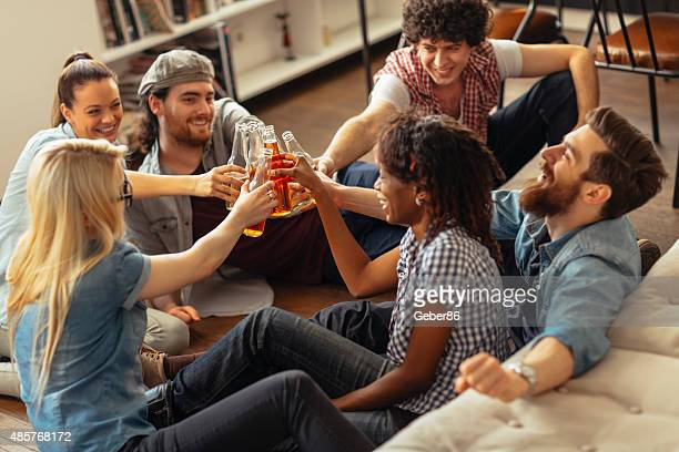 Photo of friends toasting with beerbottles