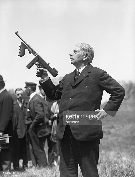 Photo of General John T Thompson demonstrating to an interested crowd of officials his new invention the antibandit gun an automatic rifle weighing a...