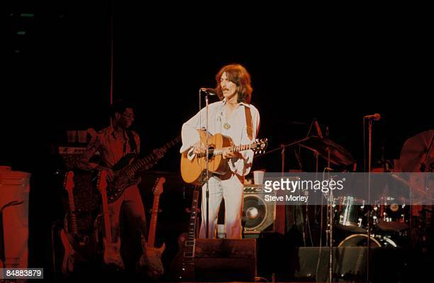 Photo of George HARRISON; performing live onstage on Dark Horse tour, playing acoustic guitar