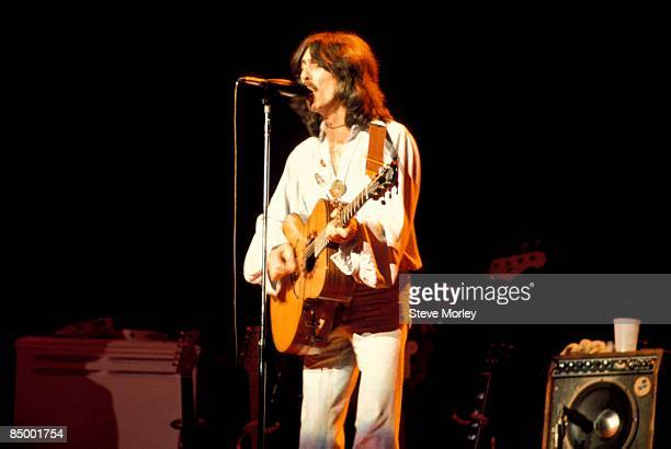 Photo of George HARRISON performing live onstage on Dark Horse tour playing acoustic guitar
