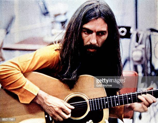 Photo of George HARRISON playing acoustic guitar c1970/1971