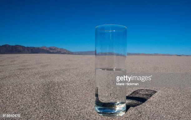 Photo of glass half empty in the desert highlighting global warming or climate change 'lack of water' issues on the planet.