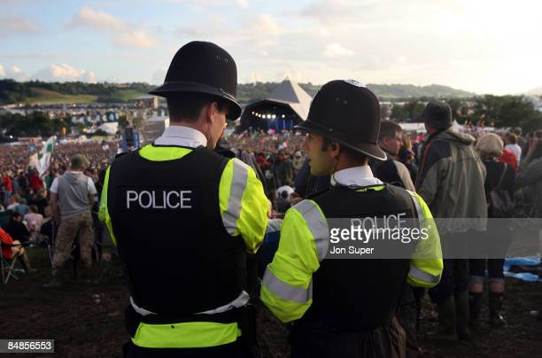 FESTIVAL Photo of GLASTONBURY two policemen at the Pyramid Stage at Glastonbury Festival with crowds in front festivals security