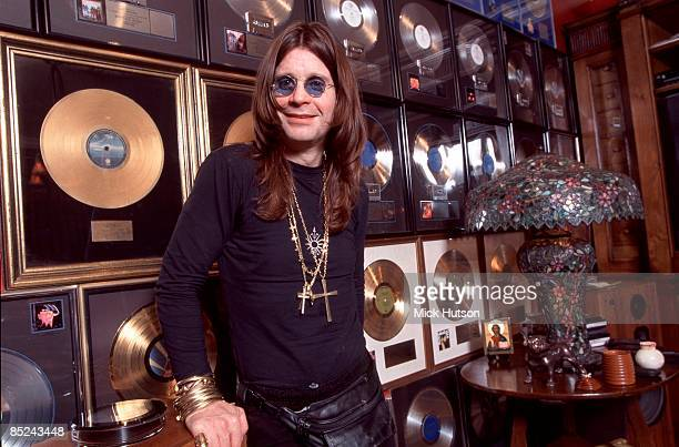 Photo of GOLD DISC and Ozzy OSBOURNE posed at home with collection of gold discs