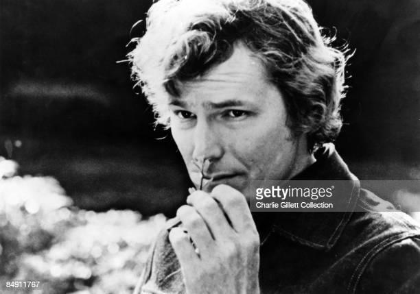 Photo of Gordon LIGHTFOOT Posed headshot smelling flower