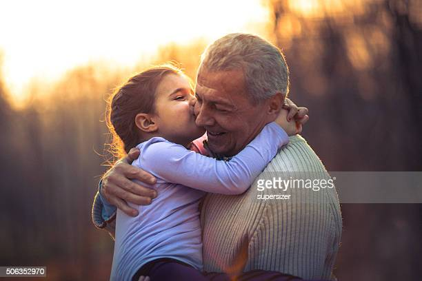 Photo of grandfather and his granddaughter in the park
