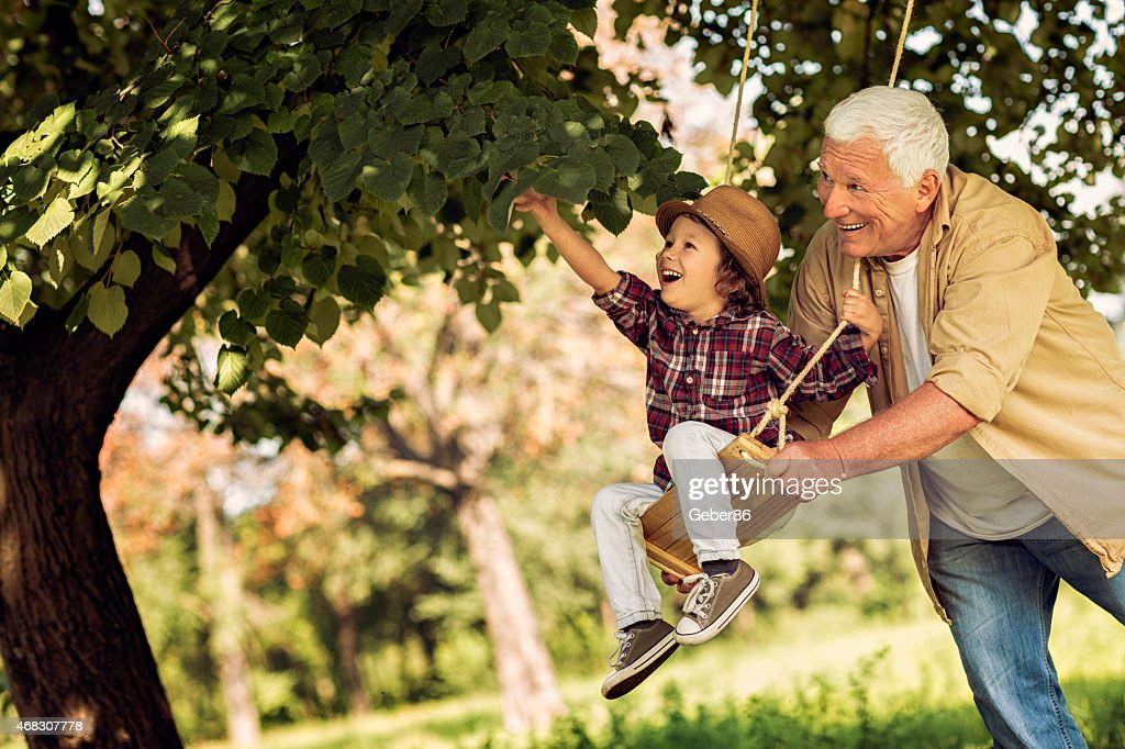 Photo of grandfather pushing grandson on a swing : Stock Photo