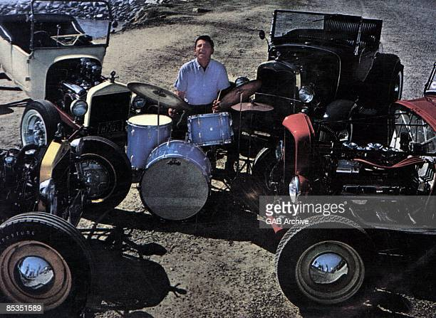 Photo of Hal BLAINE Playing the drums surrounded by vintage cars