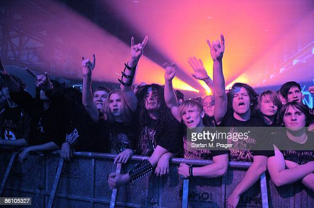 Photo of HEAVY METAL and FANS and AUDIENCE Heavy Metal fans cheering in the front row of audience at rock gig concert holding up devil horn hands