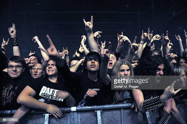 Photo of HEAVY METAL and FANS and AUDIENCE; Heavy Metal fans cheering in the front row of audience at rock gig, concert, holding up devil horn hands