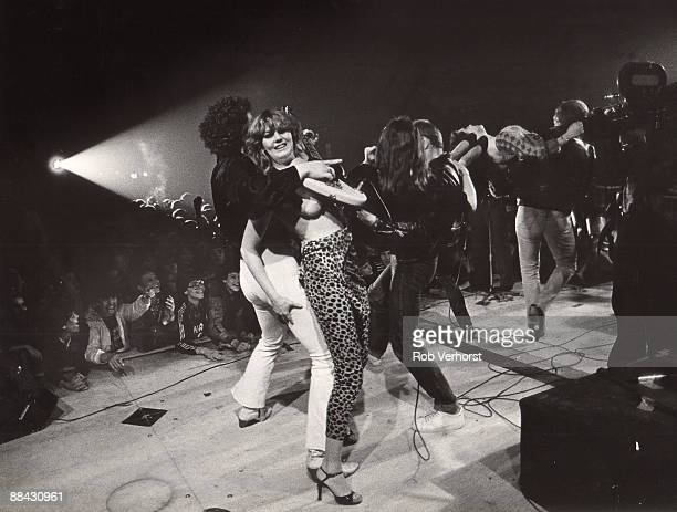 ROTTERDAM Photo of Herman BROOD Herman Brood performing on stage playing guitar around a woman audience