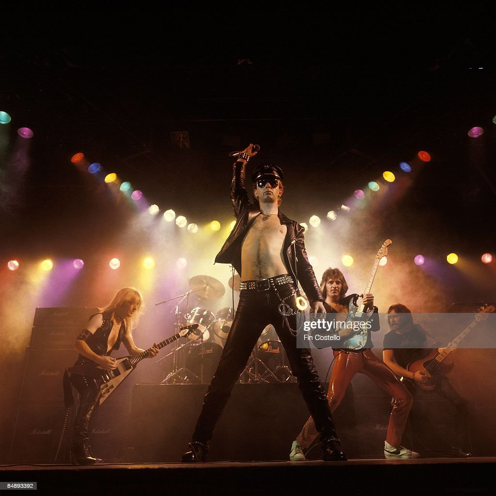 Photo of Ian HILL and JUDAS PRIEST and Rob HALFORD and KK DOWNING and Glenn TIPTON; L-R: KK Downing, Rob Halford, Glenn Tipton, Ian Hill performing on stage under stage lights - Unleashed In The East album cover session