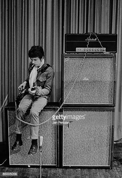 Photo of Jack BRUCE and CREAM Jack Bruce sitting on amplifiers onstage during soundcheck