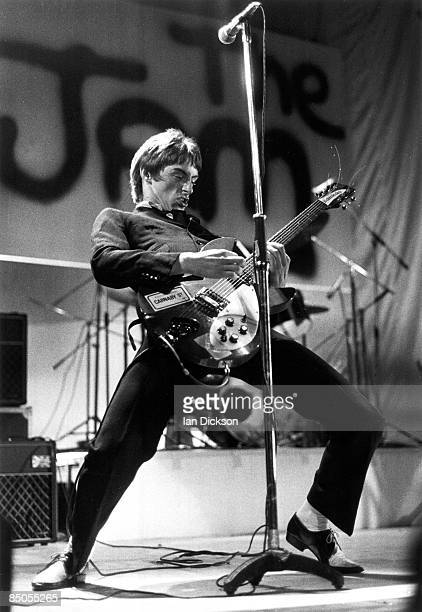 RANK Photo of JAM and Paul WELLER Paul Weller performing live onstage playing Rickenbacker 330 guitar with The Jam logo on backdrop behind