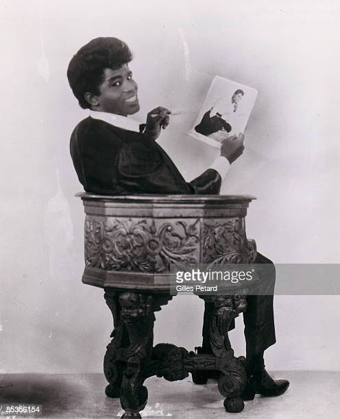 Photo of James BROWN Posed studio portrait of James Brown sitting down with photograph