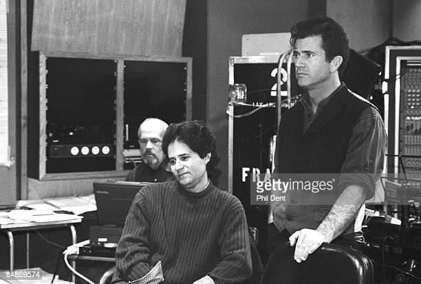 STUDIOS Photo of James HORNER and Mel GIBSON composer with sheet music at mixing desk while working on score to Braveheart film with star Mel Gibson