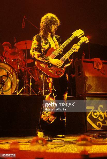 COURT Photo of Jimmy PAGE and LED ZEPPELIN Jimmy Page performing live onstage Full length holding guitar up wearing suit with dragons printed up leg...
