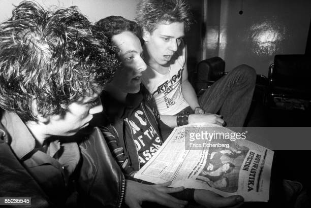 Photo of Joe STRUMMER and CLASH and Mick JONES and Paul SIMONON, L-R: Mick Jones, Joe Strummer, Paul Simonon, posed, backstage, reading newspaper -...