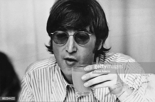 Photo of John LENNON and BEATLES John Lennon posed holding drink on final German tour