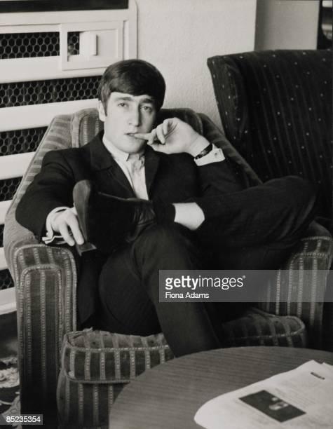 Photo of John LENNON and BEATLES John Lennon posed on armchair