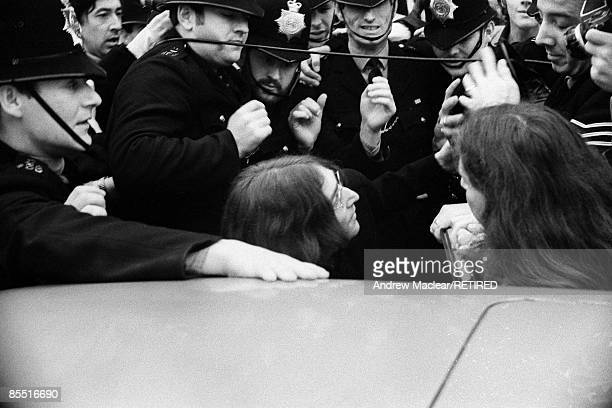 Photo of John LENNON and BEATLES John Lennon surrounded by the police as they try to get in to a car to leave Marylebone Magistrates Court after...